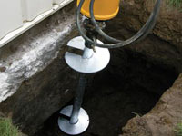 Installing a helical pier system in the earth around a foundation in Kenosha