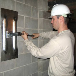 installing a wall anchor to repair an bowing foundation wall in La Crosse