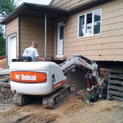 Excavating to expose the foundation walls and footings for a replacement job in Beloit