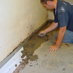 A contractor in West Allis installing a perimeter drain tile system during a sump pump installation.